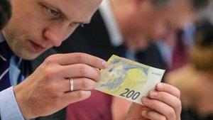 Un periodista inspecciona un nuevo de 200 euros durante lapresentación del papel moneda en la sede del Banco Central Europeo (BCE) en Fráncfort, en el 2018.