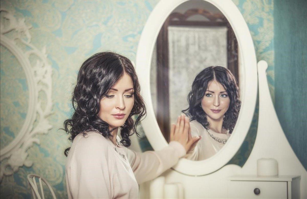 Una mujer reflejada en un espejo.