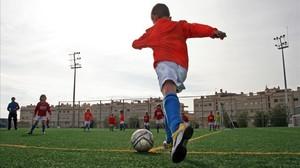 Un niño se apresta a chutar durante un partido de fútbol base.