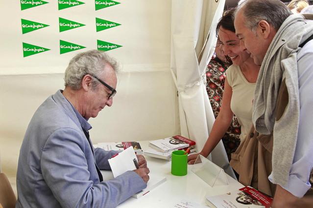El escritor Juan José Millas firma autografos a los lectores que se han acercaron a su parada para celebrar la diada en Barcelona.