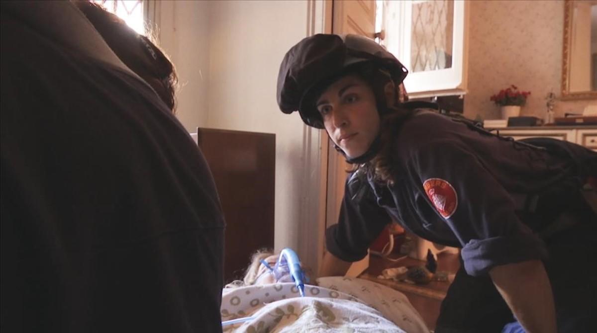 Una bomberoatiendea una anciana que se ha caído en su casa, en la serie Emergències.
