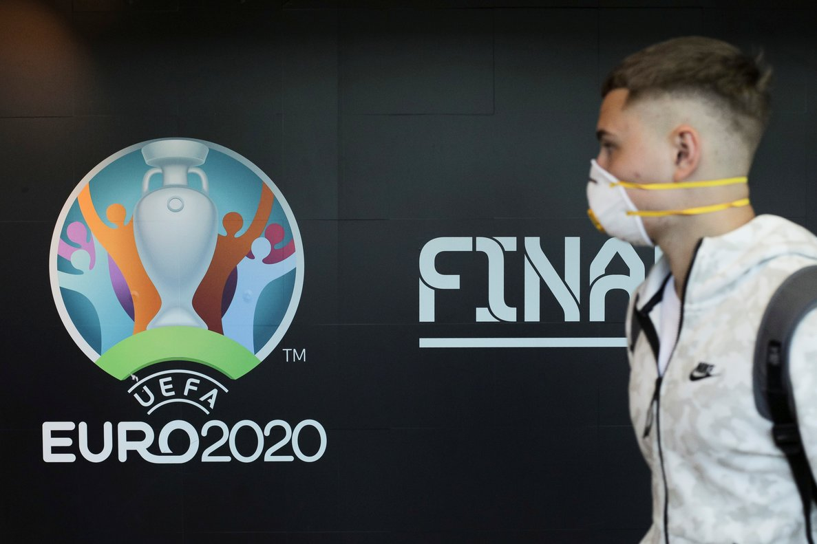 Travellers pass by a logo of the 2020 UEFA European Football Championship displayed on a wall inside Bucharest Henri Coanda International Airport, in Otopeni, Romania, March 16, 2020. Inquam Photos/Octav Ganea via REUTERS ATTENTION EDITORS - THIS IMAGE WAS PROVIDED BY A THIRD PARTY. ROMANIA OUT. NO COMMERCIAL OR EDITORIAL SALES IN ROMANIA