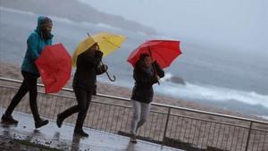 Tres dones es protegeixen del vent i la pluja a la Corunya al pas de la borrasca Ana, el 12 de desembre.