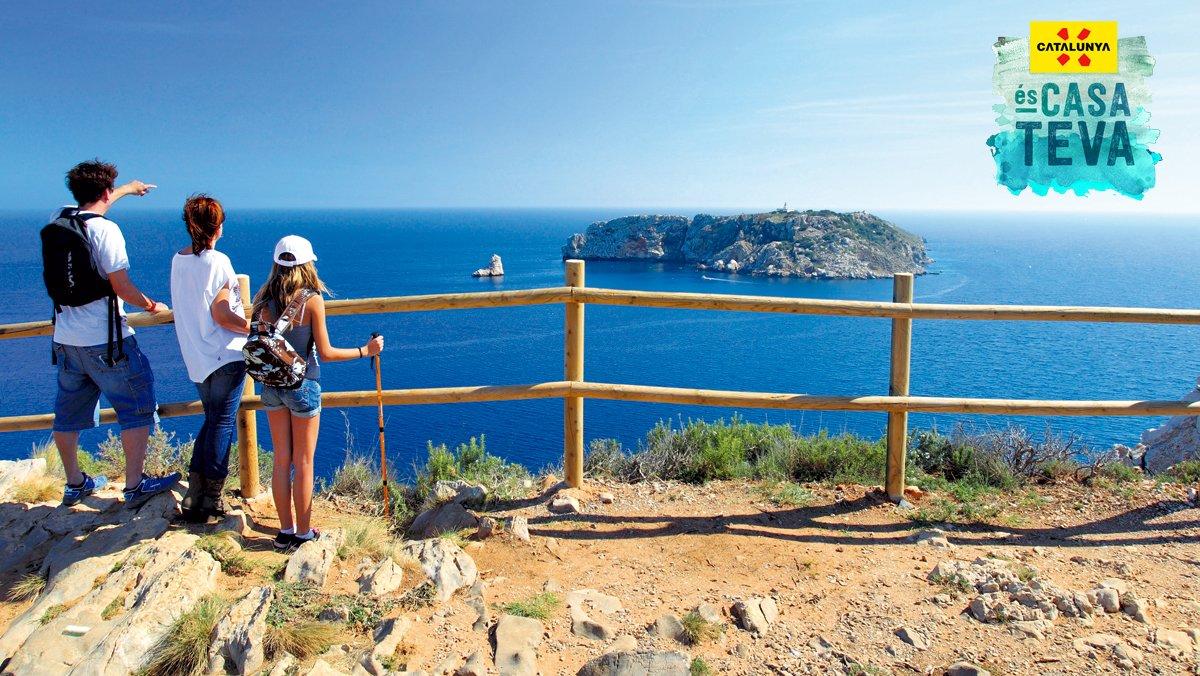 Una familia de excursionistas contemplan las Illes Medes desde un camino de ronda.