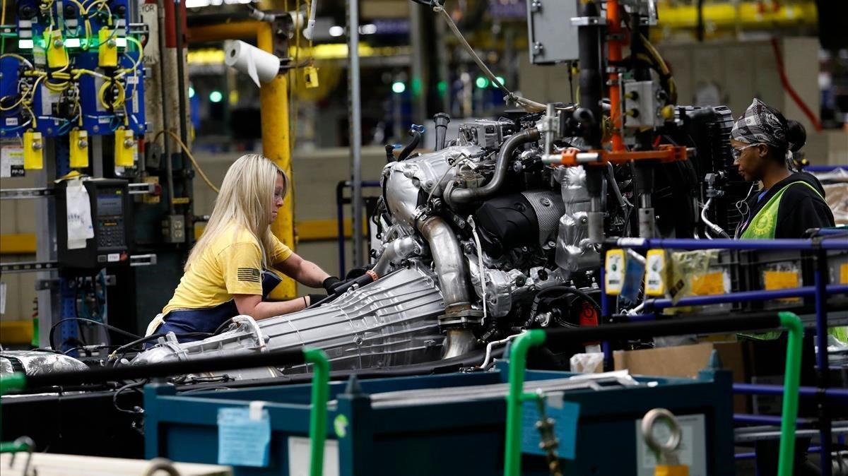 Una mujer afroamericana y otra blanca trabajan en una planta de General Motors en Flint, Michigan.