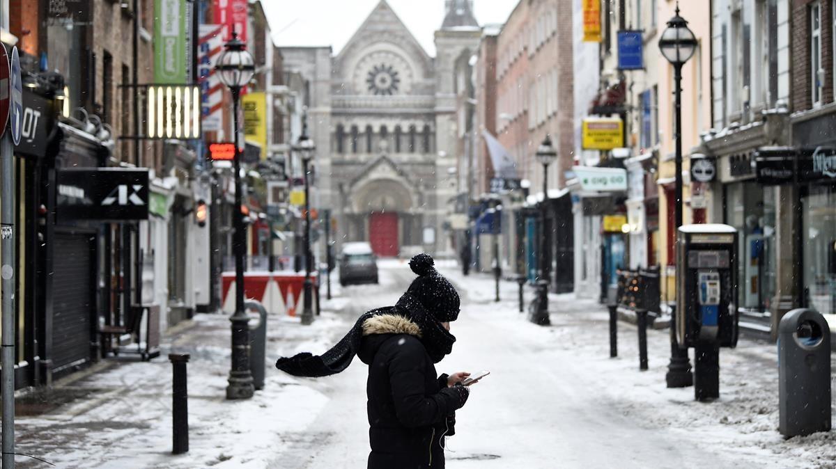 Una mujer camina por las calles desiertas de Dublín