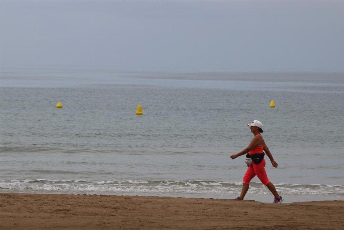 Una mujer pasea por la playa de Llevant, en Salou.