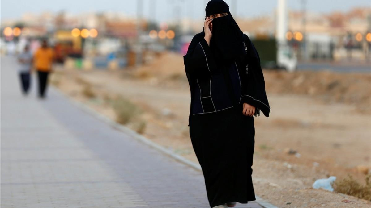Una mujer saudi habla por teléfono mientras camina por una calle de Riad.