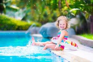 Una niña pequeña jugando en la piscina.