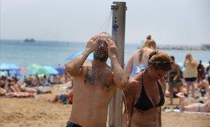 Una pareja se ducha en la playa de la Barceloneta, el verano pasado.