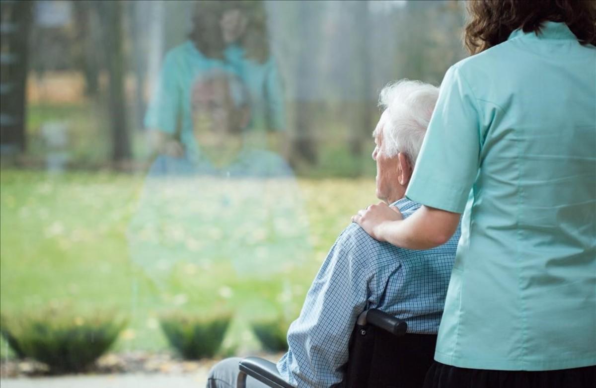 Un enfermo de alzhéimer con su cuidadora.