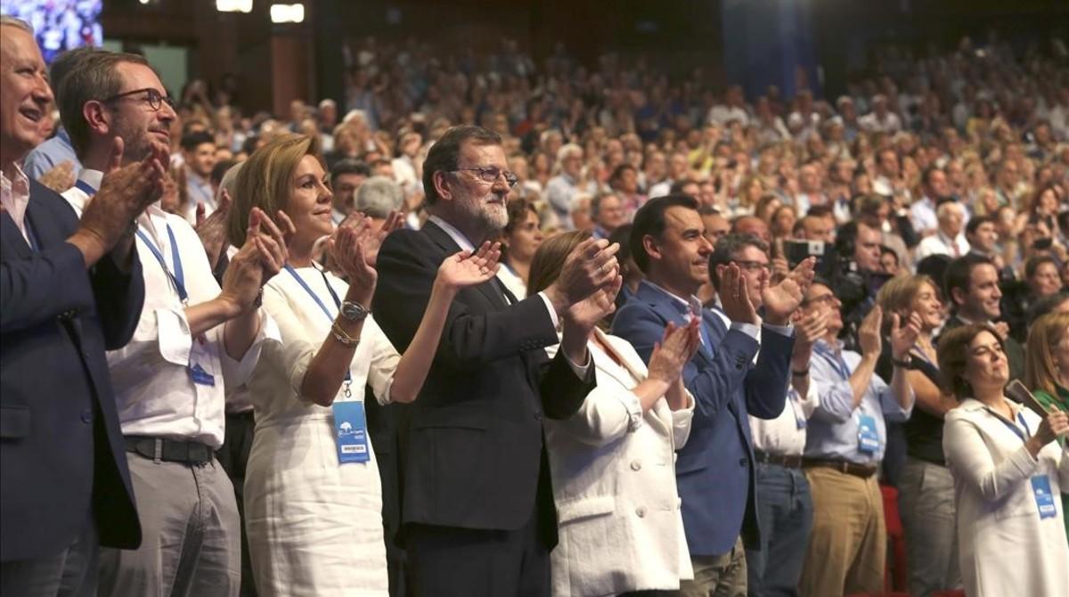 Mariano Rajoy, entre María Dolores de Cospedal (a la izquierda, en la foto) y su esposa, Elvira Fernández, durante el congreso que elegirá al sucesor del político gallego.