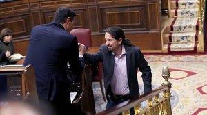 Pedro Sánchez y Pablo Iglesias se dan la mano, este sábado en el Congreso.
