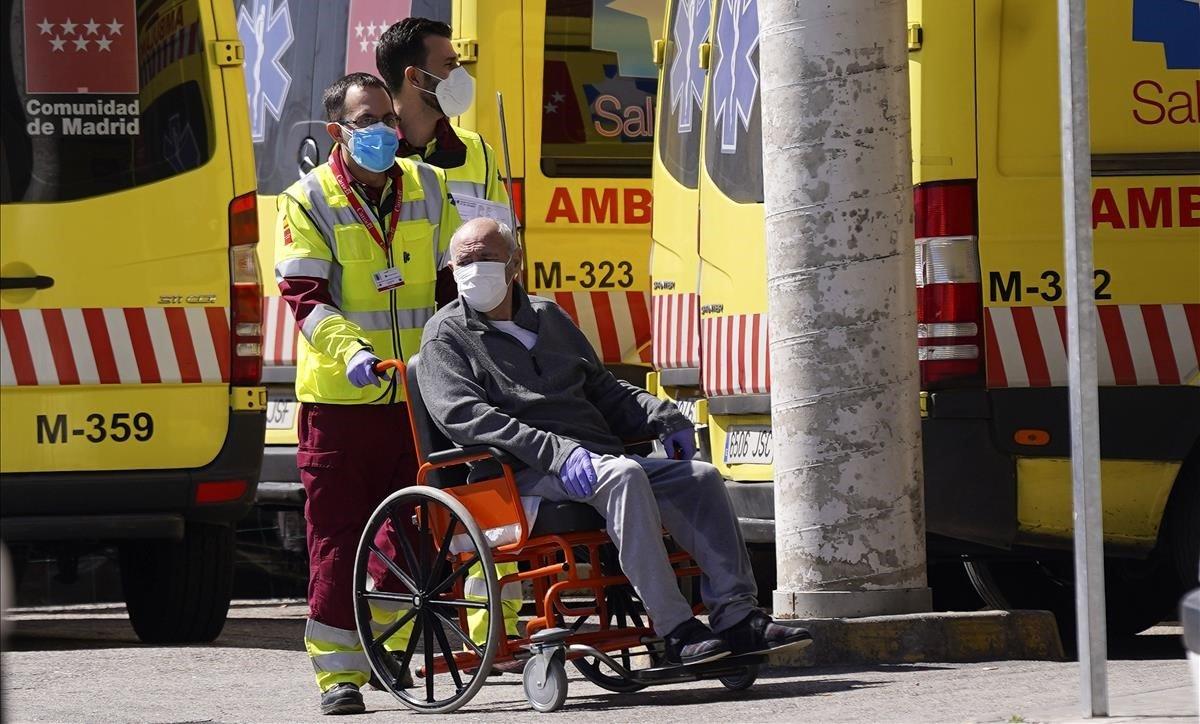 Un sanitario de ambulancia traslada a una persona mayor a la puerta del Hospital 12 de Octubre de Madrid.