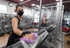 Usuaria de un gimnasio protegida con mascarilla desinfecta una cinta de correr, 19 octubre 2020