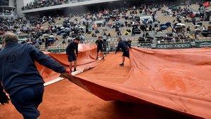 Varios operarios cubren con una lona la pista Philippe Chatrier donde jugaban Djokovic y Thiem.