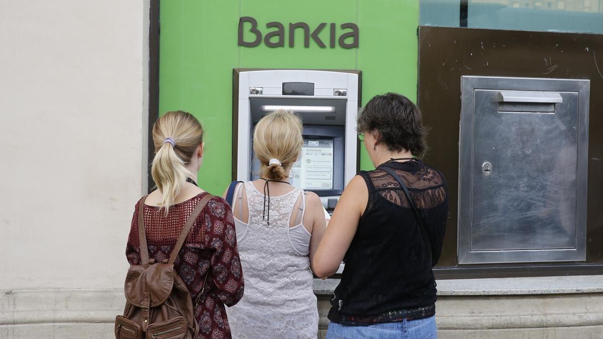 Usuarios de Bankia utilizan un cajero de la entidad en Barcelona.