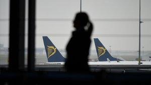 Una pasajera camina por el aeropuerto de Charleroi, en Bélgica, ante varios aviones de Ryanair.