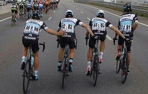 Rigoberto Urán (dreta) orina en plena carrera mentre els seus companys {le} ajuden a mantenir lequilibri, durant lúltima etapa de la Volta a Catalunya