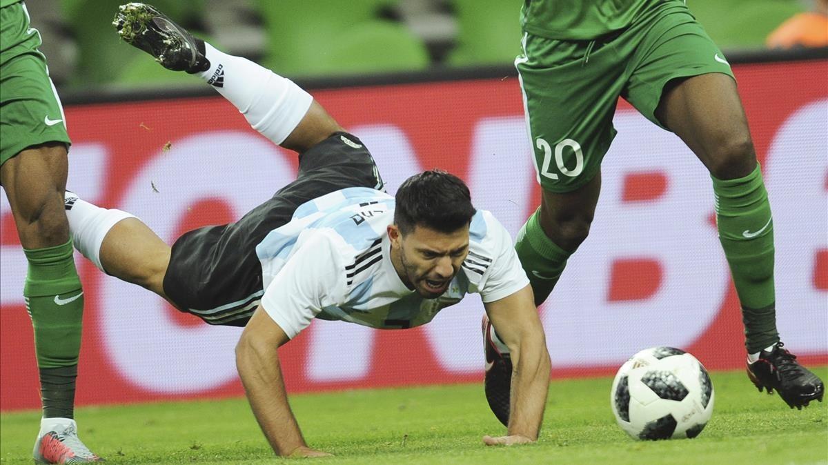 Agüero cae al suelo ante dos jugadores de Nigeria.