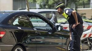 Un agente de la Policia Local inspecciona el coche en el que circulaba la mujer tiroteadael viernespor su exmarido en Zaragoza,