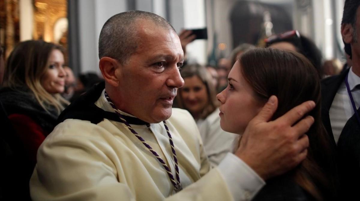 Antonio Banderas abraza a su hija, Estela del Carmen, antes de salir como penitente de Las Lágrimas. A la izquierda, la novia del actor, Nicole Kimpel.