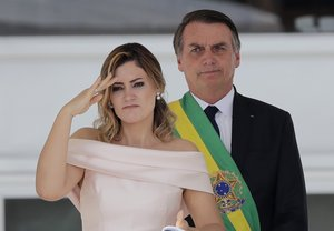 With her husband  Brazil s new President Jair Bolsonaro in the background  Brazil s new first lady Michelle Bolsonaro gives a military salute from the Planalto Presidential palace  in Brasilia. AP Photo Silvia Izquierdo