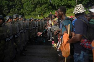 Elementos de la Guardia Nacional, policías federales y personal del Instituto Nacional de Migración (INM) detienen la marcha de unos 2.000 migrantes.