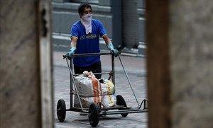 Un ciudadano de Quito trata de protegerse del contagio de coronavirus mientras traslada alimentos por el centro de la ciudad.