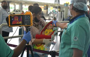 Personal del aeropuerto internacional de Bangalore toma la temperatura a una madre y su bebé, el 25 de mayo.