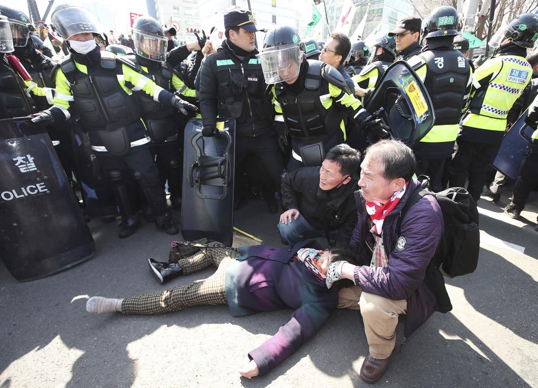 Dos manifestantes atienden a una persona herida en las protestas frente a la sede del Constitucional.
