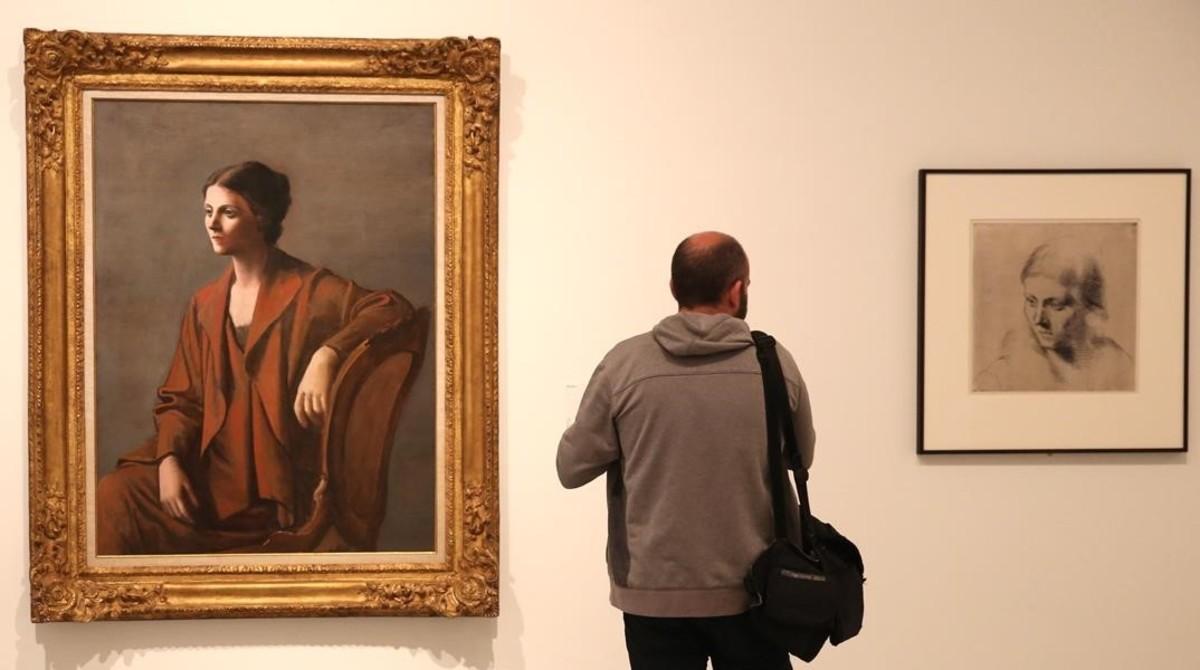 Un visitante entre dos retratos de Olga Khokhlova, a la izquierda 'Olga Picasso', una pieza muy formal y clasicista inspirada en las mujeres de Ingres.
