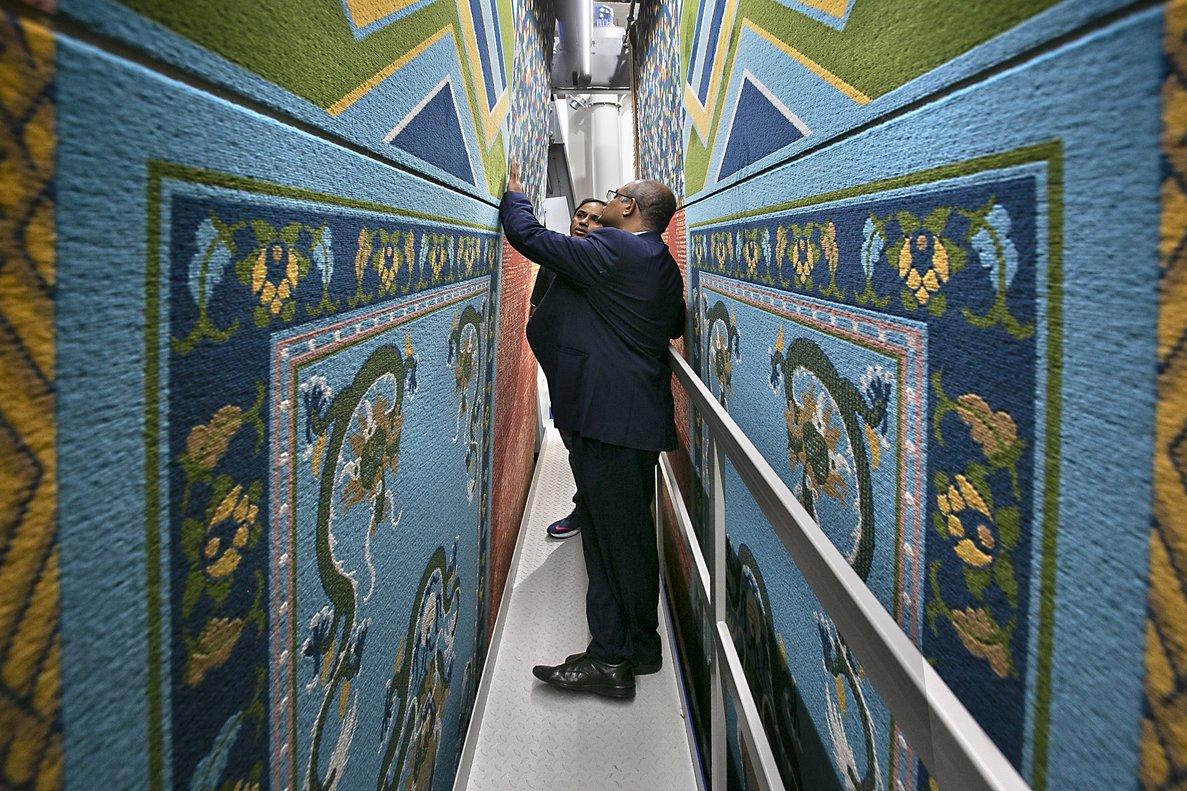 Posibles compradores analizan la calidad de las alfombras fabricadas por la máquina más grande presentada en el ITMA, propiedad de la multinacional alemana Vandewiele.