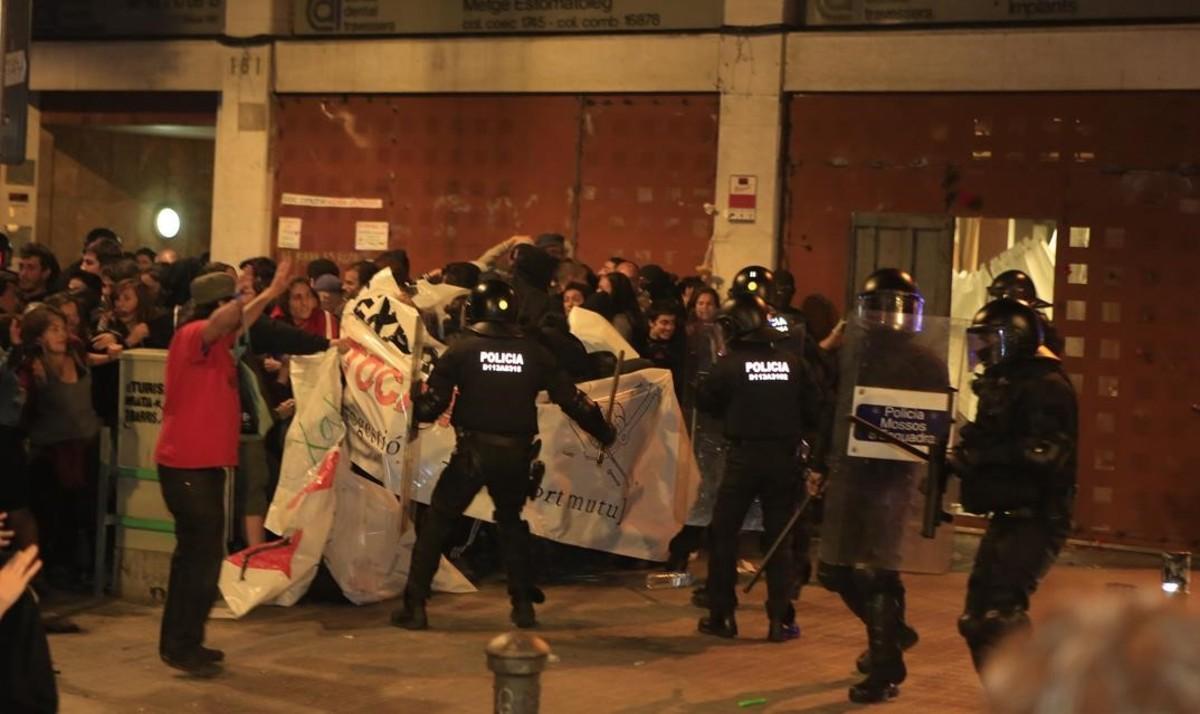 Agentes antidisturbios disuelven a un grupo de manifestantes congregados ante el local desalojado del 'banc expropiat'.
