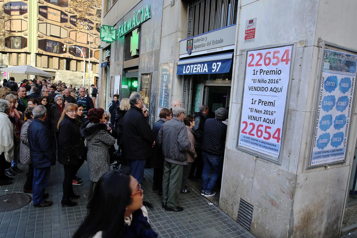 Largas colas para comprar Lotería de El Niño en la Administración nº 97 de Barcelona, en la plaza de Urquinaona.