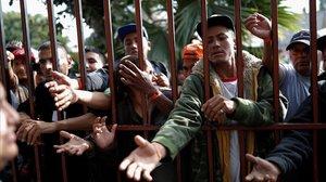 Los inmigrantes esperan una ración de comida en un refugio en Tijuana.
