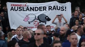 Manifestantes de extrema derecha en Chemnitz llevan un pancarta que dice Criminales extranjeros fuera!