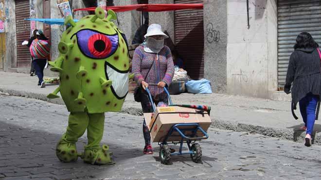 La policía de Bolivia educa a los ciudadanos con muñecos de coronavirus. En la foto, uno de los personajes se dirige a una mujer en una calle de La Paz.
