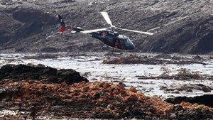 Un helicóptero busca supervivientes tras el desastre causado por la rotura de la represa que contenía residuos minerales de la compania Vale.