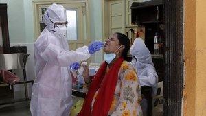 Un sanitario realiza un test de coronavirus a un trabajador en la India.