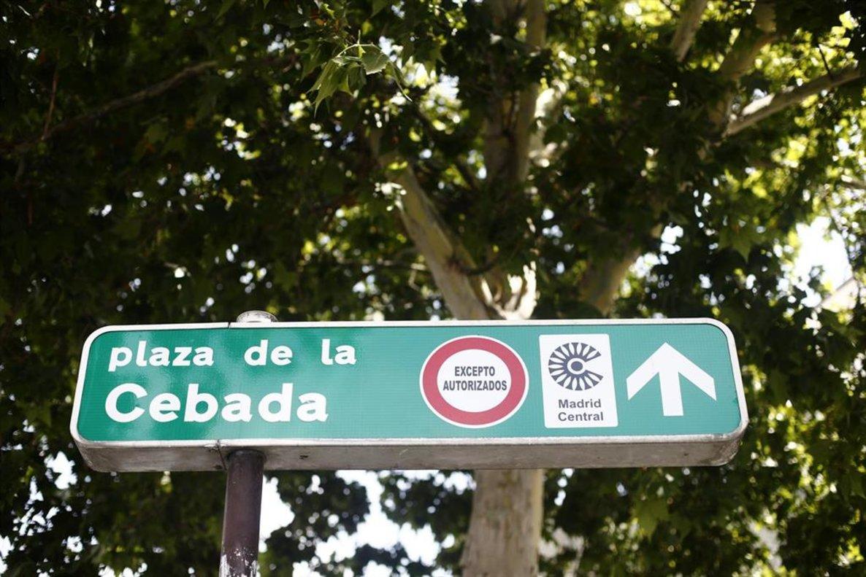 Señal de dirección con unsímbolo de prohibido aparcar al lado del distintivo de Madrid.