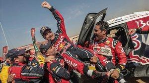 Sus amigos Stephane Peterhansel y Nasser Al-Attiyah levantan a Carlos Sainz, como ganador del Dakar-2020.