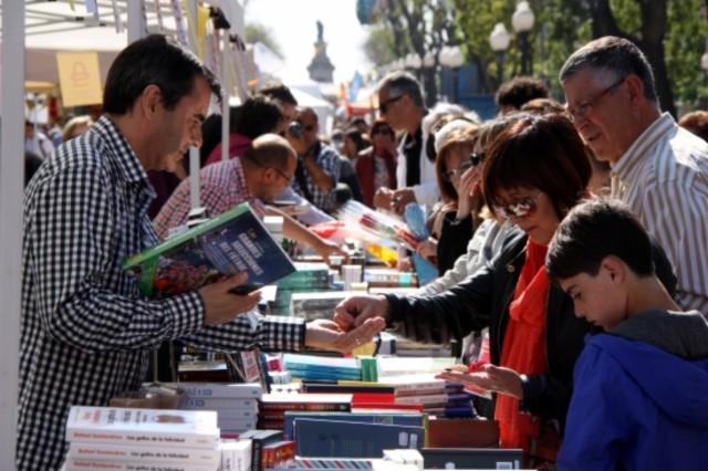 Una familia compra libros en una parada de la Rambla Nova de Tarragona.