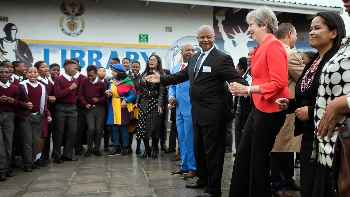 Theresa May baila con niños en su visita a Sudáfrica.
