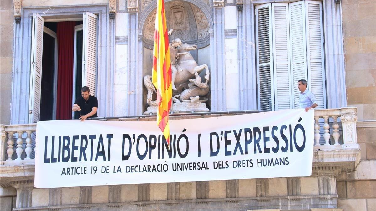 Miembros del equipo de Torra cuelgan una nueva pancarta en el Palau, tras retirar las dos anteriores: Libertad de opinión y expresión.