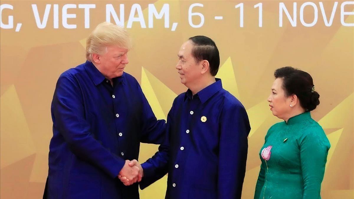 Trump (izq) estrecha la mano del presidente de Vietnam, Tran Dai Quang, junto a su esposa, en la cumbre de la APEC, el 10 de noviembre.