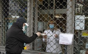 Una farmacia despacha a través de la persiana cerrada en el barrio barcelonés de Sant Andreu.