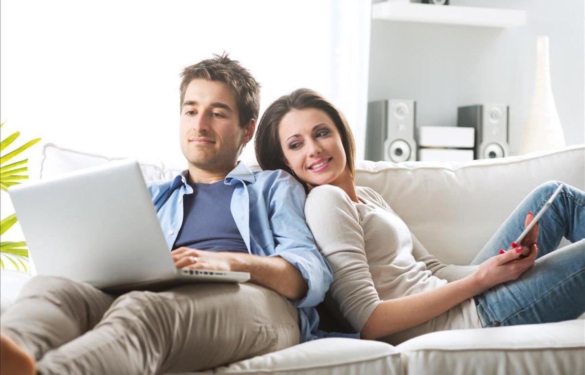 Una pareja comparte tiempo en el sofá.
