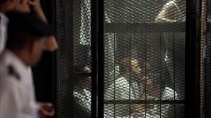 Uno de los detenidos sigue el juicio en una jaula de cristal.