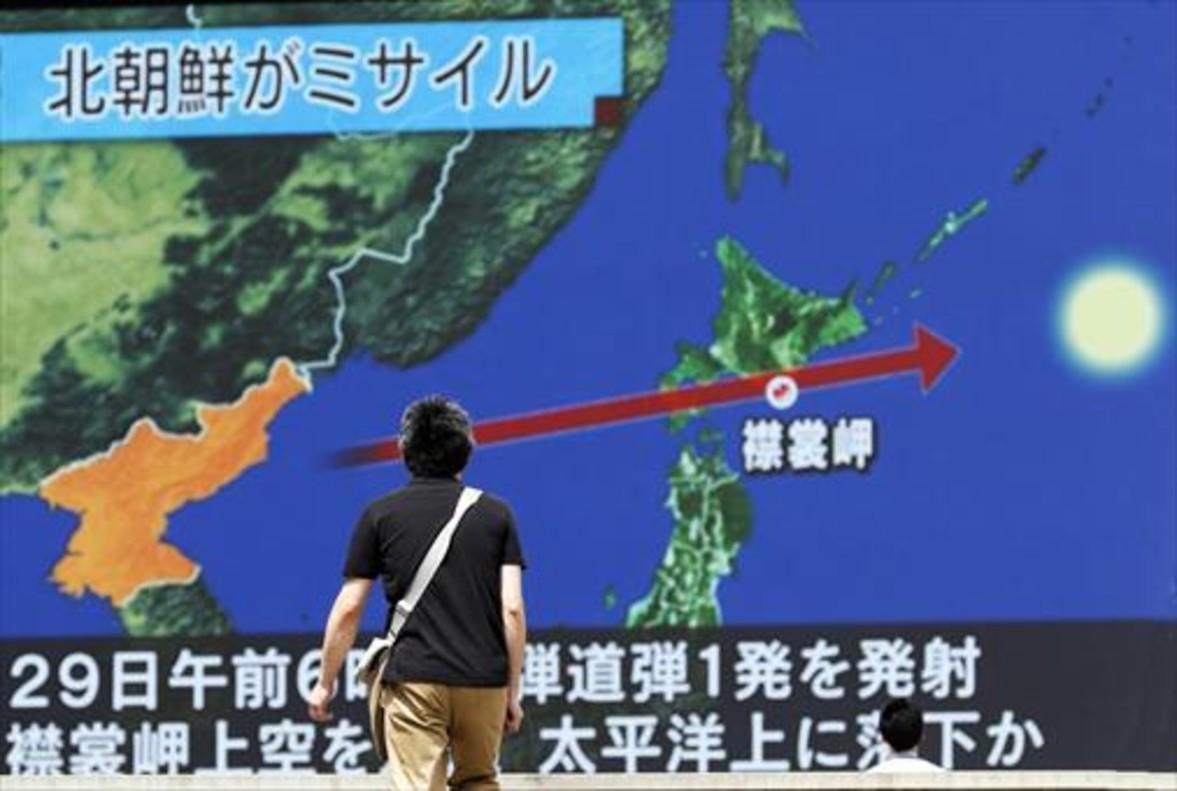 Un viandante observa la trayectoria del misil norcoreano en una pantalla gigante colocada en Tokio (Japón), el 29 de agosto.